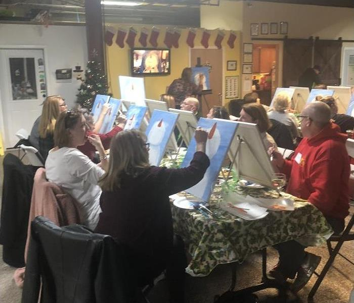 several people sitting around a table, each painting a canvass