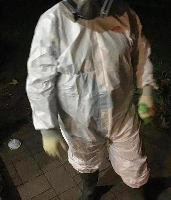 SERVPRO technician in white coveralls and gloves