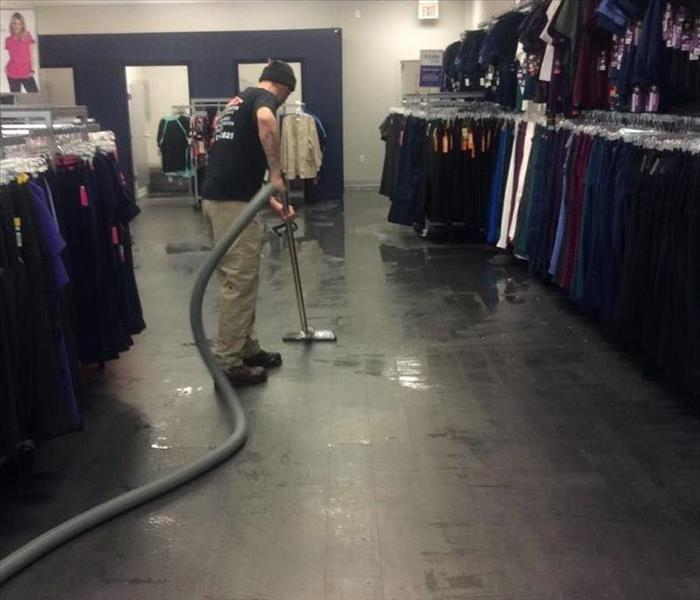 A man cleaning the floor of a business.